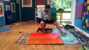 Том в своей мастерской рисует ногой